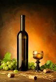 foto of wine bottle  - Arrangement of white wine bottle glass grapes vine plant corks and straw in wine cellar - JPG