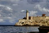 Beacon of capital of Cuba. View on beacon from quay Malecon on ocean and Havana city. Cuba island.