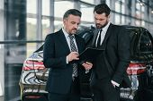 Top sales manager and customer at dealership showroom poster