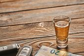 Glass of tequila or alcohol drink and car key on rustic wooden table with copy-space. Drink and driv poster