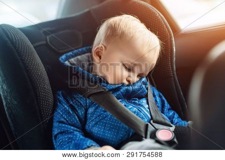 poster of Cute Caucasian Toddler Boy Sleeping In Child Safety Seat In Car During Road Trip. Adorable Baby Drea