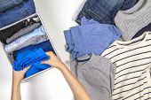 Vertical Storage Of Clothing, Tidying Up, Room Cleaning Concept. Hands Tidying Up And Sorting Kids C poster