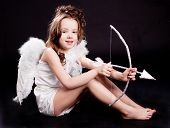 cute  six year old girl  dressed as a cupid with white wings, bow and arrow, isolated against black studio background