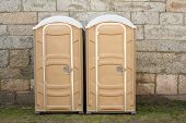 picture of porta-potties  - Two portable toilets against stone wall ports potties - JPG