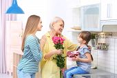 Beautiful Mature Lady, Daughter And Grandchild With Gifts In Kitchen. Happy Womens Day poster