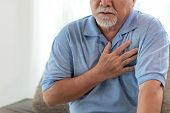 Senior Male Asian Suffering From Bad Pain In His Chest Heart Attack At Home - Senior Elderly People  poster