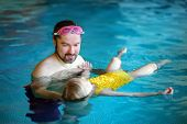 Happy Father Teaching His Little Daughter To Swim. Active Happy Child Learning To Swim. Little Girl  poster