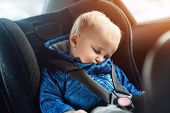 Cute Caucasian Toddler Boy Sleeping In Child Safety Seat In Car During Road Trip. Adorable Baby Drea poster