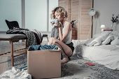 Woman Feeling Emotional Packing Clothes Of Her Ex Boyfriend poster