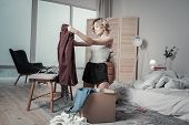 Woman Packing Clothes Of Ex Husband Into Boxes And Crying poster