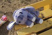 Little Blue Fury Bag For Kids In Shape Of Sweet Bunny Lay On Bench In Park poster