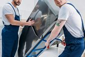 Cropped View Of Two Movers Using Hand Truck While Transporting Refrigerator In Apartment poster