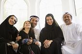 Middle Eastern Family Sat Smiling Together At Home