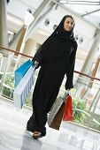 Middle Eastern Woman Walking Through Shopping Mall With Bags