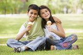 Middle Eastern Children Sat In Park With Ice Creams