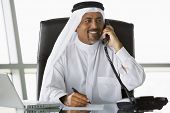 Middle Eastern Business Man On Phone At Desk With Laptop