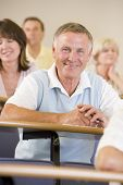 stock photo of senior men  - Man sitting in adult classroom with students in background  - JPG