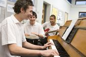stock photo of cornrow  - Student musicians practising in classroom - JPG