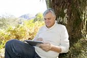 Senior man leant againt tree websurfing on internet with tablet