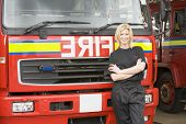 Firewoman Standing In Front Of Fire Engine