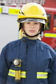 Firewoman Standing By Fire Engine Wearing Helmet