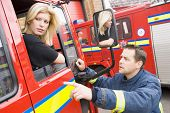 Fireman Pointing Something Out To Firewoman Sitting In Fire Engine