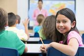 stock photo of tweeny  - Student in class looking at camera with teacher in background  - JPG