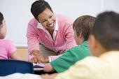 Teacher Helping Student In Class (Selective Focus)