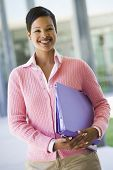 Teacher Standing Outside School Holding Binders And Smiling (Selective Focus)