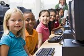 picture of school child  - Children at computer terminals with teacher in background  - JPG