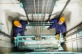 stock photo of elevator  - two machinist worker technicians at work adjusting lift with spanners in elevator hoist way - JPG