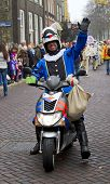 Motorcycle Policeman Dressed In Costume Waving To The Kids