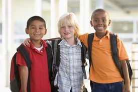 stock photo of playground school  - Three students outside school standing together smiling  - JPG