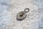 image of cartographer  - Old compass on a cartographic map of mountains - JPG