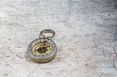 pic of cartographer  - Old compass on a cartographic map of mountains - JPG