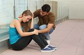 stock photo of sorrow  - Beautiful teenager girl worried sitting on the floor and a boy comforting her - JPG