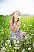 girl on field with dandelion