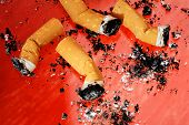 Cigarette Butts with ashes on red background.