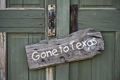 stock photo of redneck  - Gone to Texas sign on old green door - JPG