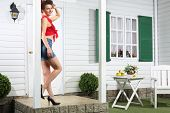 foto of girl next door  - Smiling woman in shorts stands next to white entrance door of country house - JPG