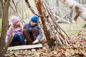 Little boy and girl sit in hut built between birches in autumn park and talk