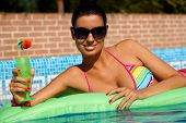 Sexy woman laying on airbed in swimming pool, smiling, sunbathing.