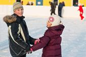 Brother and sister skating on rink hand in hand in winter