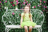 Little happy girl sits on white retro bench near verdant hedge.