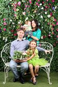 Family of four sit on white bench with bunch of flowers in garden near verdant hedge.