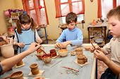 Group Of Children Decorating Their Clay Pottery