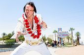Elvis impersonator man dancing by in front of Welcome to Fabulous Las Vegas sign on the strip. Peopl
