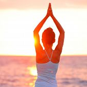 Meditation Yoga woman meditating at beach sunset or sunrise relaxing in yoga pose. Serene relaxed fe