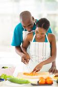 lovely afro american couple chopping tomato together in kitchen