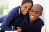 portrait of happy african couple in nightwear on bed